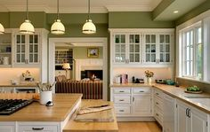 Fresh kitchen colors. White kitchen cabinetry with wooden furnishings and green walls by neva