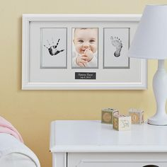 "Capture your little one's tiny hand and footprint impression in this classic white wood frame. There's a window for baby's 6""L x 4""W photo in the center. Frame measures 12""L x 18-1/2""W comes complete with a white beveled mat and mess-free ""clean-touch"" ink pad. We personalize it with any name and any date, up to 24 characters each. For wall mount."