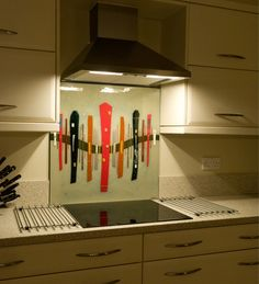 Featured in a West Midlands home, this bespoke fused glass kitchen splashback features a twist on our popular Dalaman design. With a thick red stripe down the centre of the piece, and a colour matched background to ensure the art's cohesion with the kitchen's decor, a range of colours both subtle and bold accent the creative, interesting look of the glass. Sitting as the centerpiece of the kitchen, the piece is the first thing you notice and is certainly a worthy addition.
