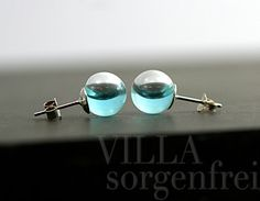 These mini hand-blown glass orbs are filled with real blue turquoise water. Theyre closed with small sterling silver caps. The ear stud setting