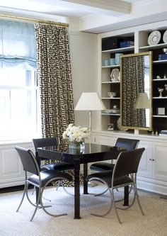 Office with ivory and chocolate brown Greek key pattern fabric curtains and white built-ins with back of shelves lined with black paper. Gilt mirror, glossy black square table and black leather chairs.