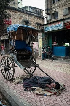 Rickshaw driver taking a nap on the streets of Calcutta, India.