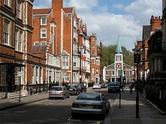 streetscape in London with brick buildings trimmed in stone on either side of the street and a church with a weathered copper steeple at the end