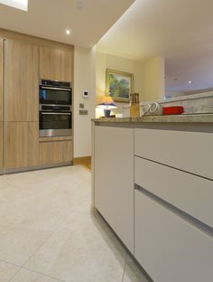 A Schuller kitchen with Champagne Matt base units and Samo Oak Natural Brown Imitation larder units topped with an Estoria Granite worktop. The colours, aluminium plinth and lighting help to create an excellent first impression on everyone who sees this kitchen.