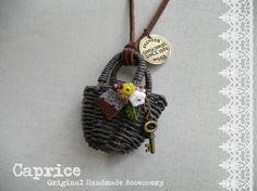 エコクラフト(紙バンド)でこげ茶色のミニチュアマルシェバッグを作りました。バスケットには、お花のビーズ・革タグ・鍵を飾っています。革ひもを通し、ネックレスにし...|ハンドメイド、手作り、手仕事品の通販・販売・購入ならCreema。
