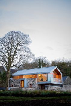 Glass stone small home cabin with lenty of light and a modern but rustic feel.  Loughloughan Barn / McGarry-Moon Architects