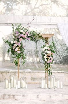 Elegant wedding arch. Gorgeously decorated natural wood trellis covered in overgrown wild and romantic greenery, vines, and pink, purple, and white flowers. Made romantic by adding tall pillar candles in varying sizes of glass vases. Super dreamy for a spring wedding