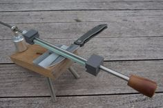 Knife Sharpening Jig by xbow -- Homemade knife sharpening jig constructed from steel rods, lumber, a coupling nut, and a rod end. http://www.homemadetools.net/homemade-knife-sharpening-jig-9