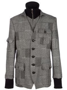 Grey wool blend jacket from VIvienne Westwood featuring a patchwork of herringbone patterns, a ribbed black funnel neck and wristcuffs, a front zip fastening underneath a front button fastening, three buttoned flap pockets on the front and one on the right sleeve.
