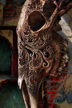Really pretty ornate bone carving on an animal skull, this tattoo would be the shit!