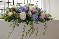 Window sill floral arrangement by Eden Blooms Florist. Lilac and pale pink hydrangea, Sweet Avalanche, Avalanche and Memory Lane roses with Phlox, Lavender and white Larkspur at Farnham Castle.