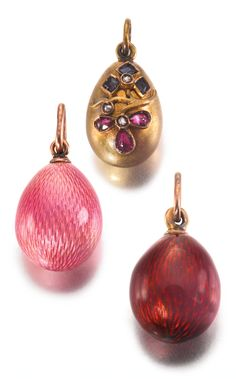 THREE FABERGÉ MINIATURE EGG PENDANTS the first enamelled in translucent pink over a hatched ground, gold suspension loop, workmaster August Hollming, St Petersburg, 1899-1903; the second of polished gold with a diamond, sapphire and ruby-set flower, struck KF; the third enamelled in translucent red over a hatched ground, gold suspension loop, workmaster August Hollming, St Petersburg; all 56 standard.