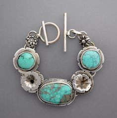 A beautiful sterling silver bracelet with three beautiful turquoise cabochons from Nevada with very nice silver flower elements. Lovely! Seven inches in length.