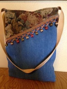 Handmade purse made from denim material and upholstery fabric. Purse is asymmetrical in that the top measures 11 across and the bottom is 8 1/2