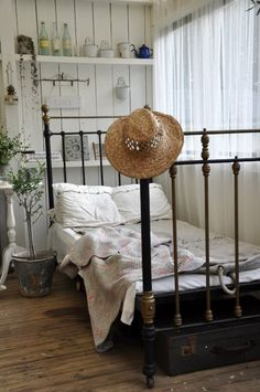 White wood plank walls, cast iron bed,