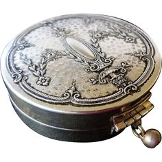 1920s Art Deco dance wrist compact is made of silver with a wonderfully elegant repousse floral design on the lid and lattice pattern on the bottom.