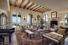 The home has a more Tuscan feel, which comes through here with the ornate fireplace, exposed beams, and dramatic windows.