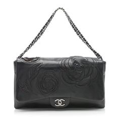 This collectible Chanel flap is made from exquisite black lambskin with red tweed inlays underneath the petals and gunmetal hardware. Details include woven chain straps, a back pocket, and iconic CC turn-lock closure. The three-compartment interior is lined in red satin with one zippered pocket. Carry this style with the straps doubled-over or pulled through.