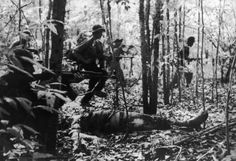 Why Did the US Enter the Vietnam War?: Viet Cong troops advance past the body of a US soldier, 1967