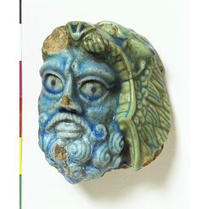 An ancient Egyptian faience head of Hercules wearing a lion skin, a symbol of power and protective amulet in wartime. (Victoria & Albert Museum)
