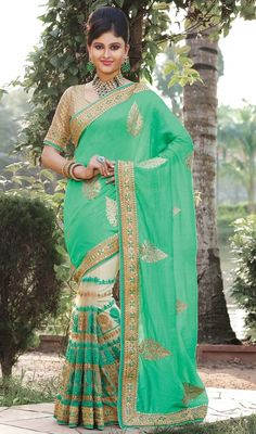 Look like a new discovered star dressed in this parrot green and cream color embroidered net silk sari. The ethnic lace, resham and stones work to your saree adds a sign of magnificence statement for the look. #embroideredbuttaworksari #reshamworksaris #embroideredhalfnhalfsaree