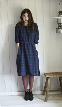 Black and indigo plaid dress made from woven organic merino wool. Pin tucked on shoulders and drawstring waist for altering fit. 2 side pockets. Texture of material is similar to cheesecloth. Fairtrade/ethical hand crafted product. 100% wool. Dry clean only. from Plumo