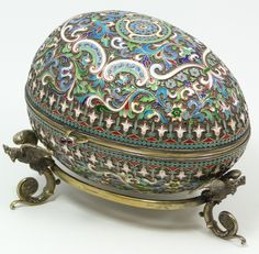 Russian silver hinged enameled egg box having elegant scrolled floral design throughout. Clasp set with two round cabochon cut garnet jewels. Gold wash interior. Includes fitted stand with three figural double headed eagle feet. Piece holds Cyrillic Pavel Akimov Ovchinnikov workmaster marks.