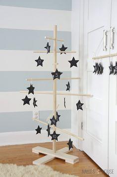 schwarze Sternenanhänger auf dem Tannenbaum aufhängen