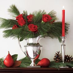 Roses, evergreen branches, pears and magnolia leaves in sparkling silverware