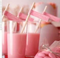 """A Pretty Pink and Gray Dessert Table  A dessert bar wouldn't be complete without milk! Amy Atlas  filled glasses with strawberry milk and added """"Be Mine"""" stirrer sticks to finish them off."""