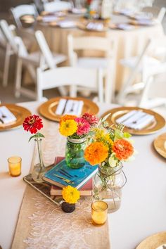 Colorful zinnias in bottles and jars atop vintage books and a burlap and lace runner {Pearlsnap Photography}