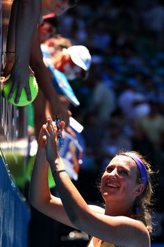 Victoria Azarenka of Belarus signs autographs for fans after winning her Quarterfinal match against Svetlana Kuznetsova of Russia during day ten of the 2013 Australian Open at Melbourne Park on January 23, 2013 in Melbourne, Australia.