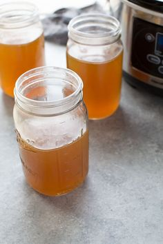 Jars of slow cooker bone broth with crockpot in background.