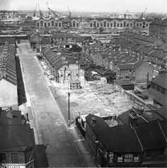 A view of an area of Silvertown showing a sunny, but deserted street, with a large gap amongst the houses on the right hand side, the result of a bomb during the Blitz. Several dogs can just be seen in the road. In the bottom right hand corner of the photograph, a stationer's and tobacconist's shop can just be seen: it appears to belong to J W Forrest. In the bottom left hand corner is a branch of Barclay's Bank. Victoria docks can be seen in the background.