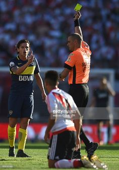 Referee Diego Abal shows the yellow card to Fernando Gago of Boca Juniors during a match between River Plate and Boca Juniors as part of Torneo Primera Division 2016/17 at Monumental Stadium on December 11, 2016 in Buenos Aires, Argentina.