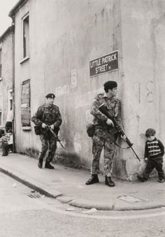 Pics on A little boy walking to his friends encounters British soldiers around the corner in Belfast, Northern Ireland. little boy walking to his friends encounters British soldiers around the corner in Belfast, Northern Ireland. Northern Ireland Troubles, Belfast Northern Ireland, British Soldier, British Army, War Photography, Vintage Photography, Wedding Photography, Boy Walking, Walking Tour