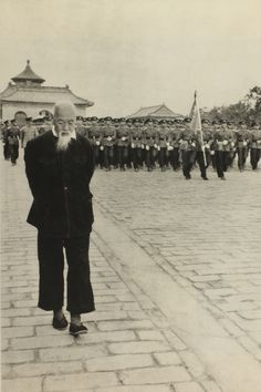 """Rehearsal of the parade for the National day (October, 1st) on the Sacred Way, a large way which goes from the Hall of Prayers (in the background) to the Temple of Heaven, Beijing from """"China I've seen"""" photobook, 1956 by Hiroshi Hamaya"""