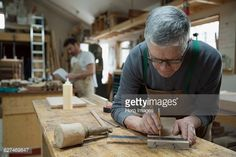 Stock Photo : Carpenter measuring and marking wood piece in workshop