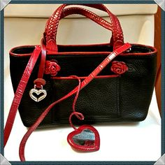 """Brighton Leather Crossbody Purse Black pebbled leather handbag. Crossbody strap is 24"""".Leather in perfect cond. Inside fabric: great cond. Braided leather double handles: 5"""". Slip pocket in back. Pocket in front holds small, heart shaped, leather enclosed mirror, attached w/ braided leather strap. Two 1.25"""", leather roses decorating the front. Small leather key strap w/ clip inside purse; metal has a few scratches. Not noticeable. Logo heart fob is present and in good cond. Bag is in overall…"""