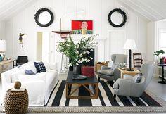 Decoração de casa de praia. Na sala sofá branco, poltrona cinza, mesa de centro de madeira com flores e adornos.