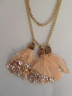 Es un sencillo collar de cadena dorada a la que van engarzadas cinco grupos de plumas.                   Los materiales son:    Ca...