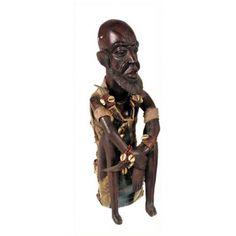 FIGURA AFRICANA  Figura africana tallada en madera representando una figura masculina. Con adornos en tela y distintos abalorios. Con tocado. Medidas: 50 cm.