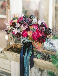 Winter Berry bouquet with ribbons running down and pops of crimson, magenta and blue