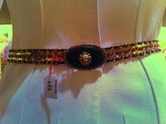 CHANEL, HAUTE COUTURE Ceinture chaine en métal doré entrelacée de cuir rouge, marine, boucle ovale sertie de pâte de verre à l'imitation onyx rehaussé de tête de lion