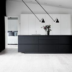 ET Hus med kontraster - det lyse @dinesen gulv, den matsorte køkkenø og hvide skabsvæg - smukt akkompagneret af de ikoniske La Lampe Gras…