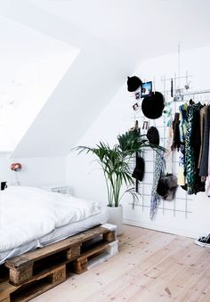 Ultra Sleek, Minimal Bedroom With DIY Palette Bed, White Linens And An  On The Wall Wire Storage Center
