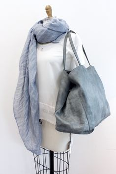A soft gray leather bag big enough to fit all of your essentials. Unlined with handles that fit over your shoulder, one inside pocket, and snap closure.