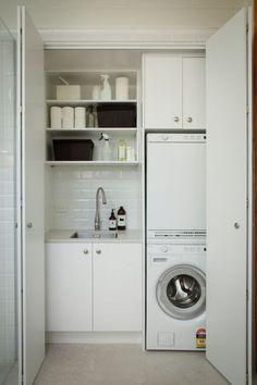 Também com as máquinas de lavar e secar uma sobre a outra, a minilavanderia branca foi montada em um nicho. O charme fica por conta dos subway tiles, dos cestos e dos recipientes para sabão sobre a pia.