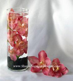 Submerged pink cymbidium orchids with black river rocks