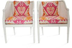 Paint vintage faux bamboo and cane chairs high gloss white and add pink and orange ikat cushions
